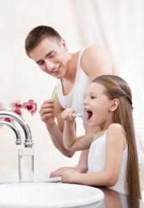 Vater und Tochter bei der täglichen Zahnpflege