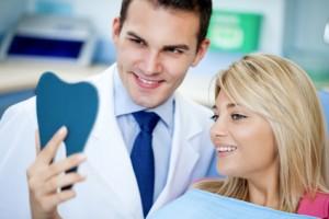 Zahnarzt und Patientin überprüfen den Sitz der Prothesen