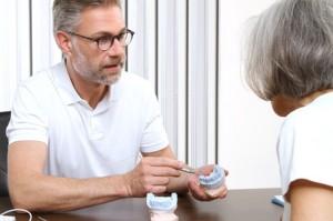 Ein Zahnarzt erläutert die Risiken einer Implantatversorgung